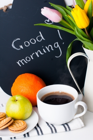 good life: bouquet of tulips in a white jug, morning coffee, fruit and chalk board with the inscription on a white background