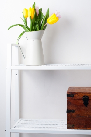 idea comfortable: home interior decoration  a bouquet of tulips in a jug and a wooden box on white shelves Stock Photo