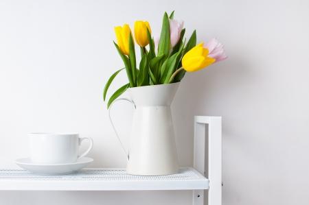 стиль жизни: украшения домашнего интерьера букетом тюльпанов в кувшин и чашки с блюдцем на белом полки