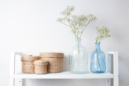 home interior decoration  the branches in vintage bottles and baskets on white shelves