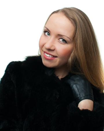 Portrait of a confident young woman in a natural fur coat on white background, isolated photo