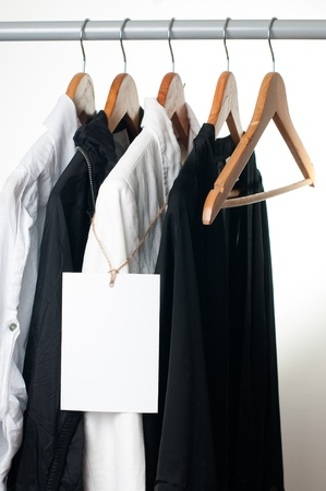 dry cleaned: Black and white clothes hanging on a rack in a row with a blank label