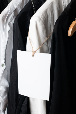 dry cleaned: Black and white clothes hanging on a rack in a row with a blank label, close-up