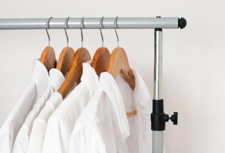 dry cleaned: Bianco vestiti puliti, camicie e giacche appese su un rack in una fila Archivio Fotografico