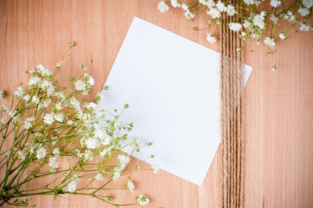 Vintage hand-made background with white flowers, white cardboard and rope on a wooden board photo