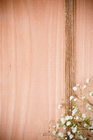 Vintage hand-made background with white flowers and rope on a wooden board photo