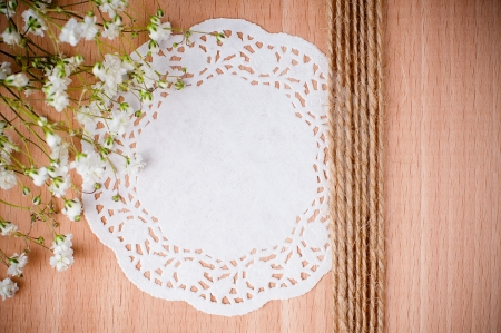 Vintage hand-made background with white napkin, flowers and rope on a wooden board photo