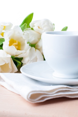 tulips in vase: White coffee cup and a bouquet of white tulips close-up, isolated Stock Photo