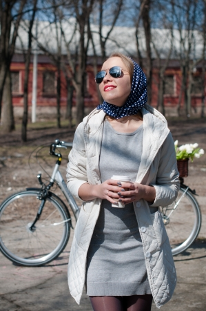 A young woman with a cup of coffee resting with a bicycle in early spring in a park, country style photo