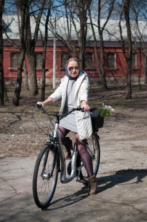 headscarf: A young woman riding a bicycle in a park in early spring