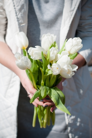 girl holding a bouquet of fresh white spring tulips, close-up photo