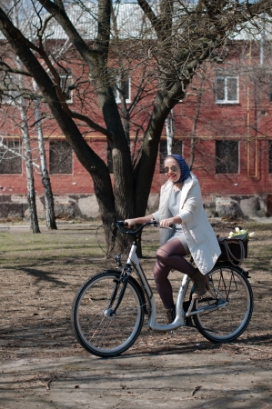 A young woman riding a bicycle in a park in early spring photo