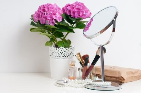 Schoonheid en make-up concept: tafel spiegel, bloemen, parfum, sieraden en make-up kwasten op een witte tafel, close-up Stockfoto