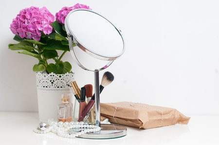 Beauty and make-up concept: table mirror, flowers, perfume, jewelry and makeup brushes on a white table, close-up