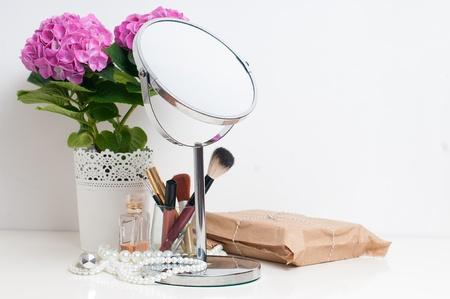 写真素材 , 美しさとメイクアップの概念 テーブル ミラー、花、香水、白いテーブルの上の宝石や化粧ブラシ クローズ アップ