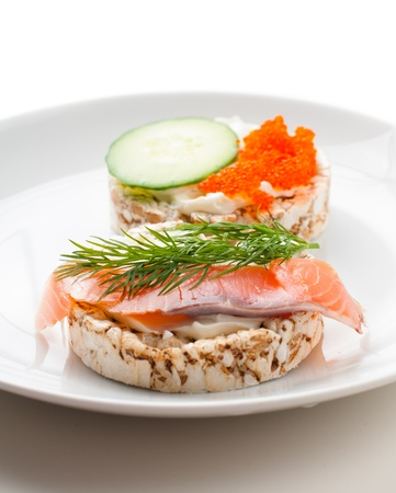Appetizers with red fish, herbs, cucumber and red caviar on a white plate, close-up photo