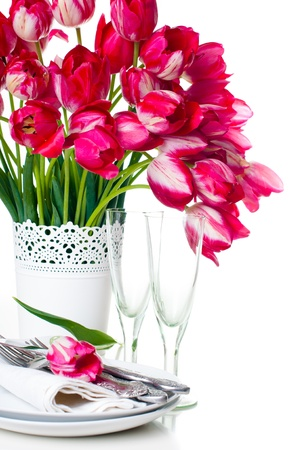 Festive table setting with a bouquet of bright pink tulips in a white vase and vintage wine glasses, isolated