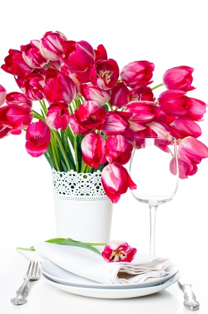 Holiday table setting with a bouquet of bright pink tulips in a vase and a glass of white, isolated