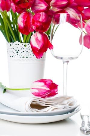 假日表设置与明亮的桃红色郁金香花束在花瓶和一杯白色,被隔绝