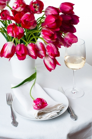 wedding table setting: Home table setting with a bouquet of bright pink tulips in a white vase, tablecloth, cutlery and a glass of wine isolated