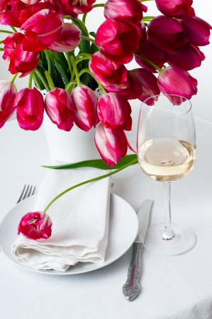 Glass of white wine and a festive table setting with a bouquet of bright pink tulips in a white vase, isolated
