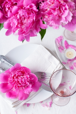 Bright festive table setting with pink peonies, candles and vintage cutlery Stock Photo - 20019061