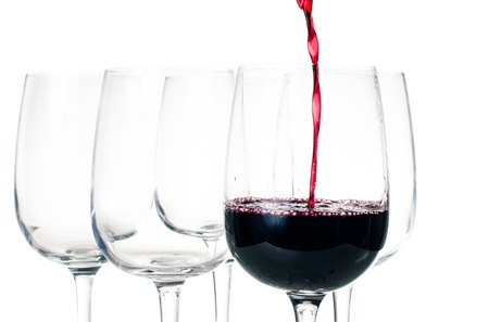 winetasting: Wine-tasting, red wine pouring into empty glass closeup on a white background, isolated