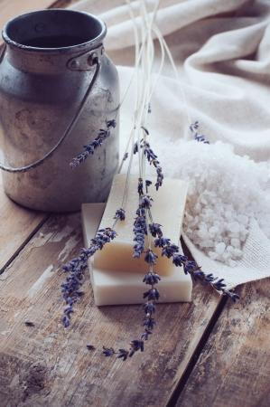 Natuurlijke zeep, lavendel, zout en oud kunnen op een houten bord, rustieke stilleven, hygiënische producten voor bad en spa
