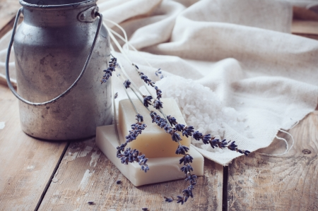 Natural soap, lavender, salt, cloth, old cans on a wooden board, rustic hygiene items for bath and spa  Stock Photo