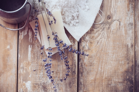 Rustic country background, natural soap, lavender, salt and old cans on a wooden board, hygiene items for the bath and spa