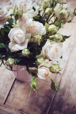 Bouquet of roses in metal pot on the wooden background, vintage style Stock Photo