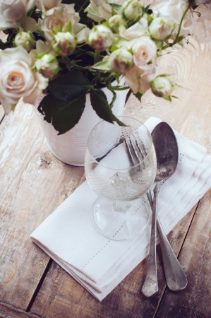 Vintage table setting with roses, antique rustic dishes and cutlery on the wooden background, close-up Stock Photo - 21168758