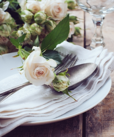 wedding table decor: Vintage table setting with roses, antique rustic dishes and cutlery on the wooden background, close-up