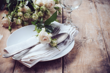flower arrangement white table: Vintage table setting with roses, antique rustic dishes and cutlery on the wooden background, close-up