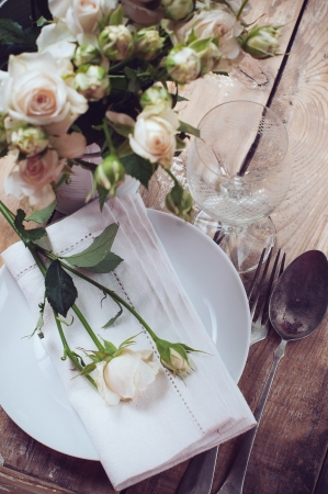 antique dishes: Vintage table setting with roses, antique rustic dishes and cutlery on the wooden background, close-up