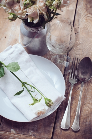 Vintage table setting with roses, antique rustic dishes and cutlery on the wooden background, close-up photo