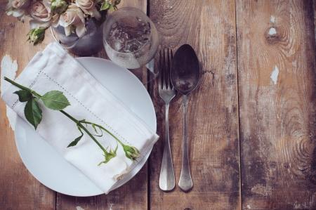 ビンテージ テーブルのバラ、アンティークの素朴な食器とカトラリー木製の背景に設定クローズ アップ 写真素材