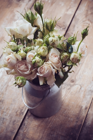 Bouquet of roses in metal pot on the wooden background, vintage style photo