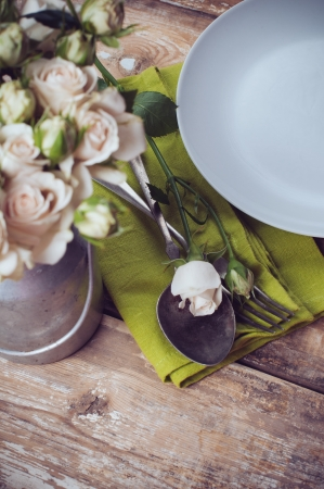 Vintage table setting with rose flowers on a linen napkin on a wooden board background, close-up photo