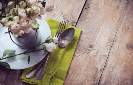 rustic: Vintage table setting with rose flowers on a linen napkin on a wooden board background, close-up Stock Photo