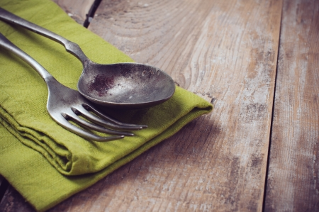 simple meal: Vintage cutlery on linen napkin against a wooden board, close-up Stock Photo