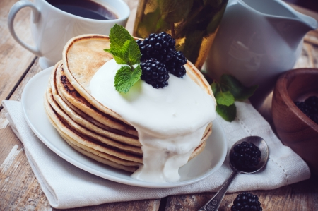 flapjacks: A stack of fresh, homemade pancakes with blackberries and whipped cream on a wooden table, a healthy breakfast, close-up. Stock Photo