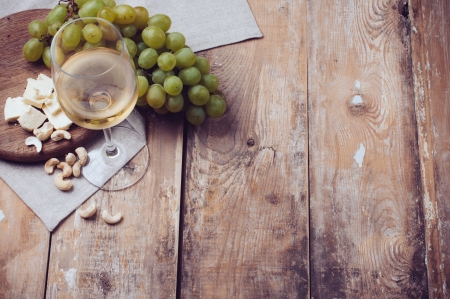 wine and grapes: A glass of white wine, grapes, cashew nuts and soft cheese on a wooden board, rustic style background