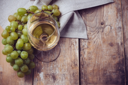 wine country: A glass of white wine, grapes, coarse linen cloth on a wooden board, closeup