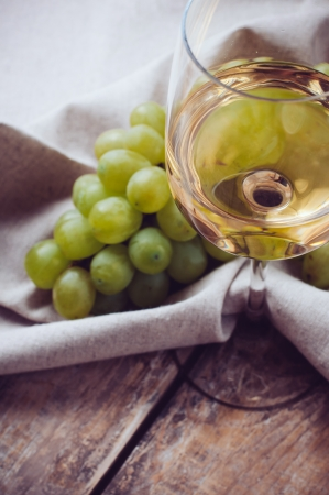 goblet: A glass of white wine, grapes, coarse linen cloth on a wooden board, extremely closeup