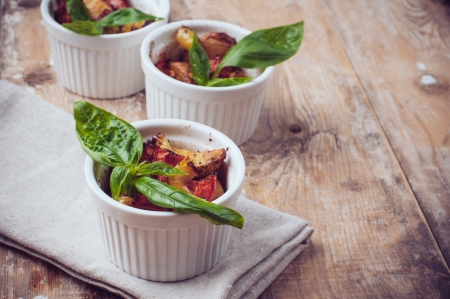 Vegan food: roasted vegetables, tomatoes, potatoes and peppers with fresh basil in ceramic forms on a wooden board photo