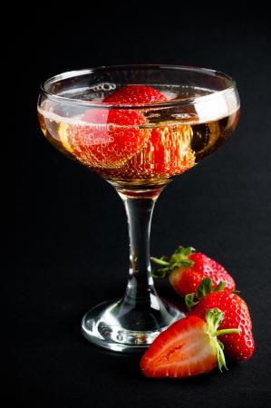 Glas koude champagne met aardbeien op een zwarte achtergrond, close-up