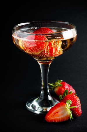 wineglass: Glass of cold champagne with strawberries on a black background, close-up