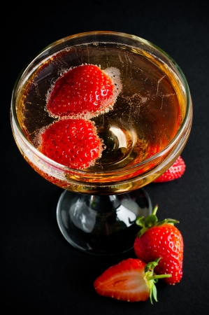 Glass of cold champagne with strawberries on a black background, close-up photo