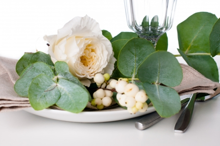 Festive table setting with floral decoration, white roses, leaves and berries on a white background Stock Photo - 22278311